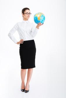 Полная длина красивой молодой бизнес-леди, стоящей и держащей земной глобус над белой стеной