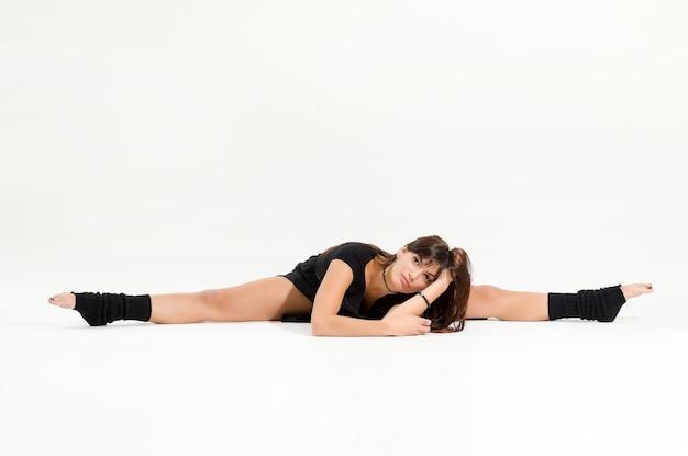 Полная длина красивой молодой женщины и современного профессионального танцора, исполняющего средний шпагат, глядя в камеру на белом фоне студии с копией пространства