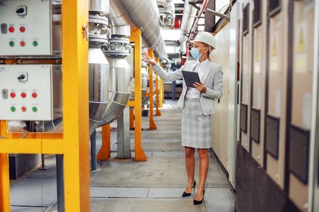 Блондинка-босс в полный рост в официальной одежде, в шлеме на голове, в защитной маске, гуляет по обогревательной установке и использует планшет для проверки механизмов.