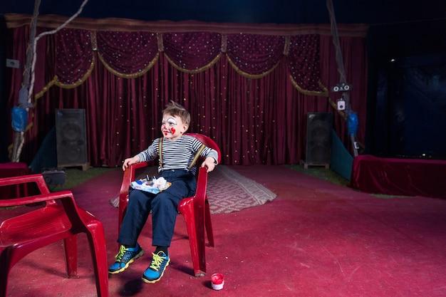 Мальчик в клоунской косметике в полный рост сидит в красном пластиковом кресле с подносом для макияжа на коленях, на пустой сцене с красным полом и занавеской на заднем плане
