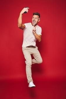 赤で隔離のスマートフォンでジャンプしてselfieを取る縞模様のtシャツのブルネットの男の全長