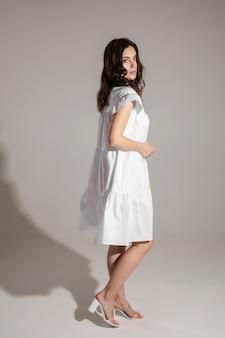 白いドレスを着て、スタジオでポーズをとっている間カメラを見ている穏やかな若い女性のフルレングス。ファッション。ショッピング。夏のコンセプト