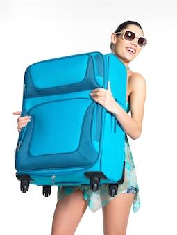 カジュアルな女性の全身が重い旅行スーツケースを保持します