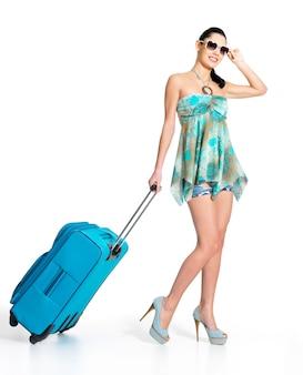 Полная длина повседневной женщины, стоящей с дорожным чемоданом