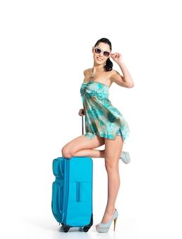 旅行スーツケースを持って立っているカジュアルな女性の全長
