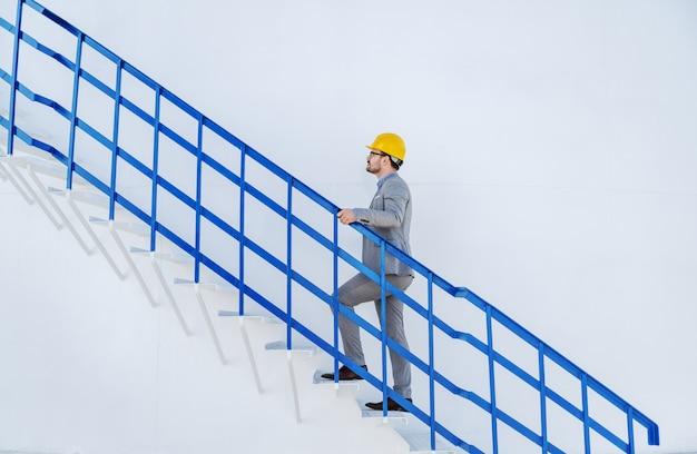 Полная длина кавказского бизнесмена в костюме с шлем на голове, восхождение по лестнице на бак с маслом.