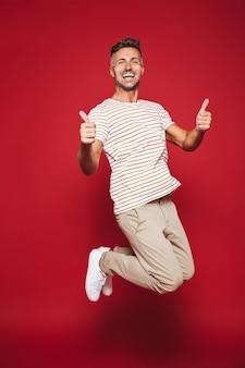 Кавказский мужчина в полную длину прыгает в полосатой футболке и показывает палец вверх изолирован на красном