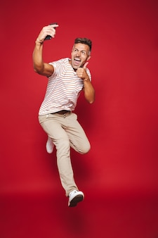 赤で隔離の携帯電話でジャンプしてselfieを取る縞模様のtシャツを着た白人男性の全長