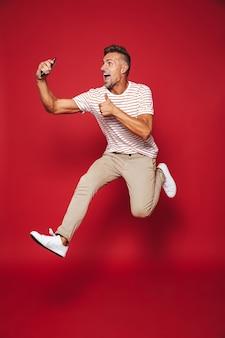 赤で隔離のスマートフォンでジャンプしてselfieを取る縞模様のtシャツの白人男性の完全な長さ