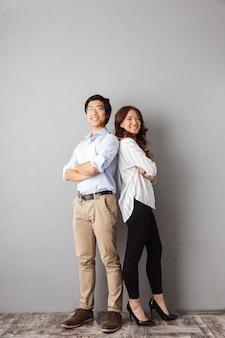 Полная длина веселой азиатской пары, стоящей спиной к спине