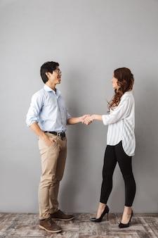 立って、握手する陽気なアジアのカップルの全長