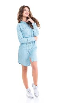 흰색 벽 위에 파란색 캐주얼 드레스와 흰색 운동화에 쾌활한 매력적인 젊은 여자의 전체 길이