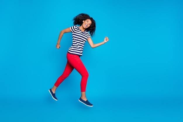 Полная длина веселой сумасшедшей афро-американской женщины в прыжке, быстро бегает