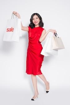 쇼핑백과 함께 빨간 드레스를 입고 쾌활한 유행 아시아 여성의 전체 길이