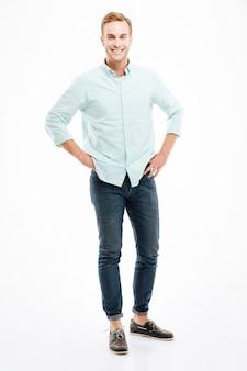 Полный рост жизнерадостного красивого молодого человека в рубашке и джинсах, стоящего и улыбающегося над белой стеной