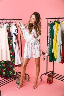 Полная длина жизнерадостной женщины в платье, стоящей возле шкафа с одеждой и выбирающей, что надеть, изолирована на розовом