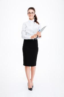 Полная длина жизнерадостной молодой деловой женщины в очках, стоящих и держащей буфер обмена над белой стеной