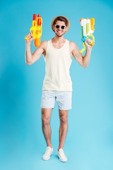 Полная длина веселого молодого человека, держащего два водяных пистолета