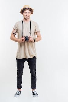 白い背景の上に古いビンテージ写真カメラを立って保持している陽気な若い男の全長
