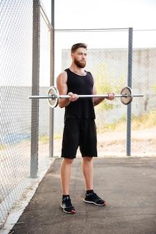 屋外でバーベルを使って運動する集中した若い男のアスリートの全長