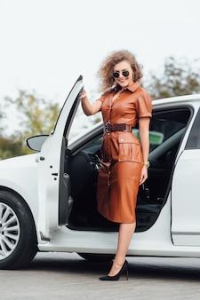 彼女の新しい白い車から出てくる自信を持って若い実業家の完全な長さ