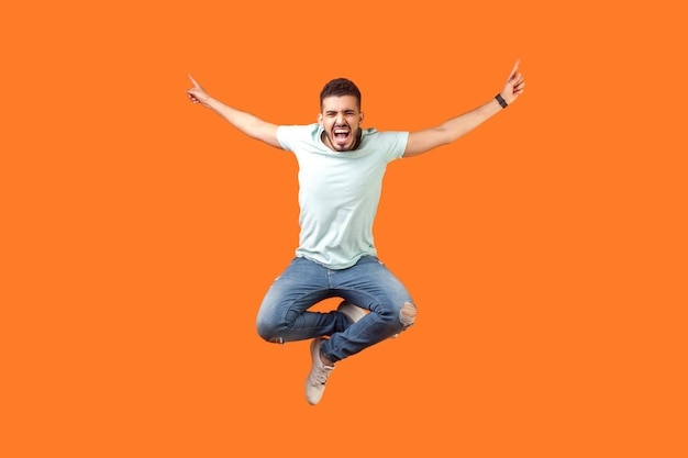Во весь рост сумасшедший, обрадованный брюнет в белом костюме прыгает в воздухе с поднятыми руками, громко кричит от радости, чувствуя себя энергичным и живым. закрытый студийный выстрел изолирован на оранжевом фоне
