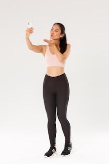 Полная длина милая и глупая женщина-блогер в тренажерном зале, одетая в спортивную одежду и делающая селфи или прямую трансляцию с тренировки в тренажерном зале, отправляя воздушный поцелуй на экране мобильного телефона, стоя на белом фоне.