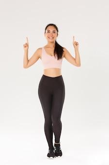 スポーツウェア、スポーツのような女性アスリート、指を上に向けて、トレーニングトレーニング機器、白い背景で広告を見ている完璧なボディを持つかわいいアジアの女の子の全長。
