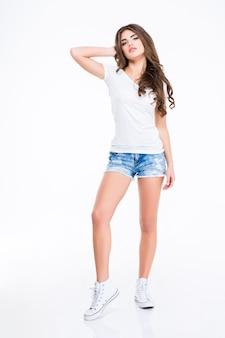 흰색 티셔츠, 청바지 반바지와 흰 벽 위에 서있는 운동화에 긴 곱슬 머리를 가진 귀여운 사랑스러운 젊은 여성의 전체 길이