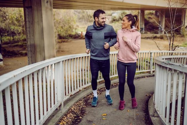 専用のスポーティな若いカップルの完全な長さの橋を上り、ジョギングしてお互いを見ています。