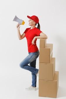 Полная длина женщины потехи доставки в красной кепке, футболке изолированной на белой предпосылке. женский курьер кричит в мегафон горячих новостей, стоя возле пустых картонных коробок. получение пакета. скопируйте пространство.