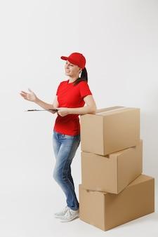빨간 모자, 흰색 배경에 고립 된 t-셔츠 배달 여자의 전체 길이. 종이 문서가 있는 클립보드를 들고 있는 여성 택배, 빈 판지 상자에 빈 시트. 패키지를 받고 있습니다.