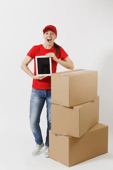 빨간 모자, 흰색 배경에 고립 된 t-셔츠 배달 젊은 여자의 전체 길이. 판지 상자, 태블릿 pc 컴퓨터, 빈 검은색 빈 화면 근처의 여성 택배. 패키지를 받고 있습니다. 공간을 복사합니다.