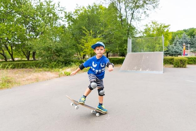 夏の日にスケートパークのスケートボードで安全パッドとキャップを身に着けている決心した少年の全長
