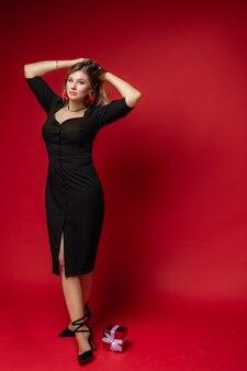 黒のドレスを着て、赤い背景、床にギフトボックスに立っているエレガントな若い女性のフルレングス。ファッション。ショッピング。夏のコンセプト