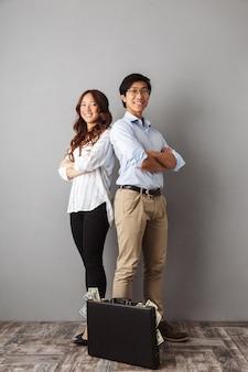 Полная длина возбужденной азиатской пары стоя, держа портфель, полный денежных банкнот