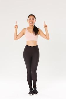 놀란 찾고 손가락을 가리키는 운동복에 흥분된 웃는 여성 운동 선수의 전체 길이, 피트니스를 즐기는 여성 운동 선수는 새로운 회원을 초대합니다.