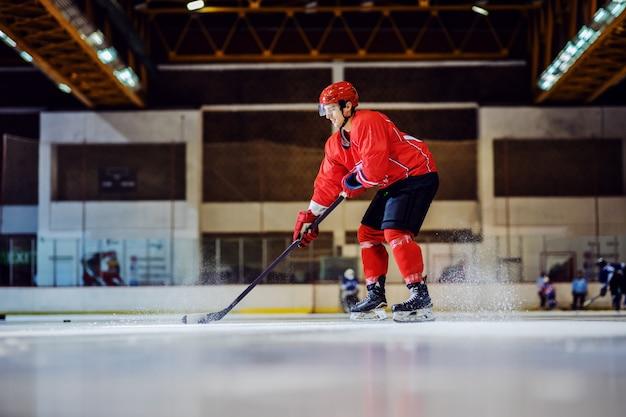 Во всю длину бесстрашный хоккеист катается на коньках и готовится отбить шайбу. интерьер зала. зимние виды спорта.