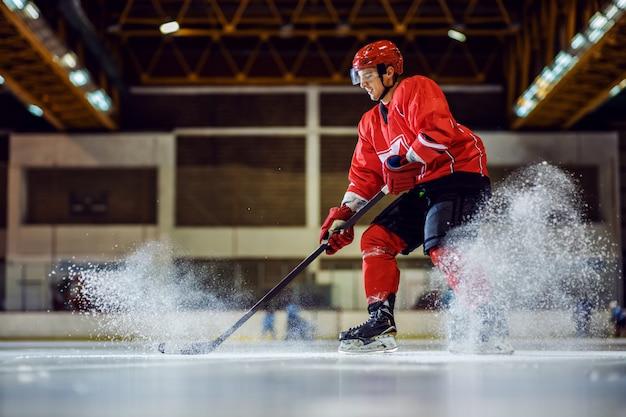 Во всю длину бесстрашный хоккеист катается на коньках и пытается забить. интерьер зала. зимние виды спорта.