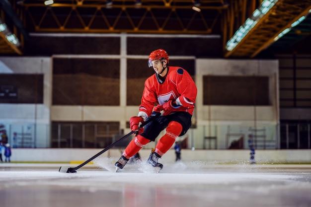 Бесстрашный хоккеист в полный рост идет к воротам и пытается забить. интерьер зала. зимние виды спорта.