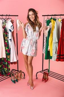 Полная длина женщины-потребителя в платье, стоящей возле шкафа с одеждой и выбирающей, что надеть, изолирована на розовом