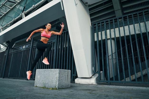 屋外で運動しながら空中に浮かんでいるスポーツウェアのフィット感のある魅力的な若い女性の全長