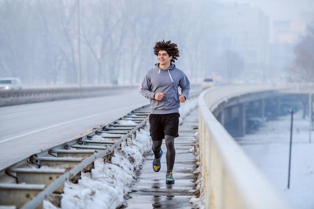 橋の上を走っている巻き毛のスポーツウェアに焦点を当てた白人フィット男性の完全な長さ。冬。屋外フィットネス。