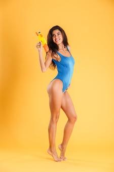 오렌지 벽에 물총을 들고 파란색 수영복에 재미 있은 쾌활한 젊은 여자의 전체 길이