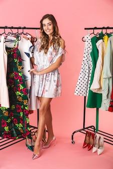 Полная длина великолепной женщины в платье, стоящей возле шкафа с одеждой и выбирающей, что надеть, изолирована на розовом