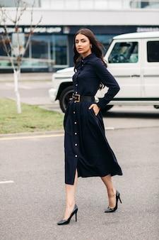 Великолепная молодая брюнетка в полный рост идет по улице в своем длинном темно-синем платье