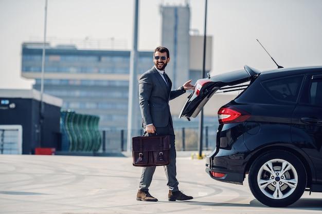 Во всю длину красивый кавказский бизнесмен в костюме и с солнцезащитными очками, держа портфель и закрывая багажник. внешняя парковка.