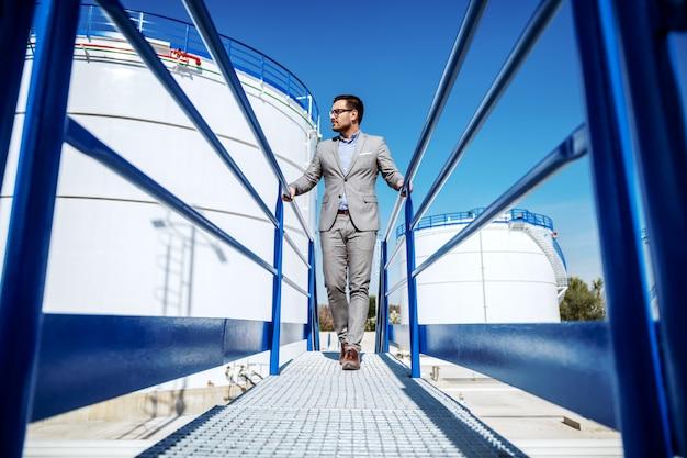 橋を渡って歩くスーツでハンサムな白人実業家の全長。