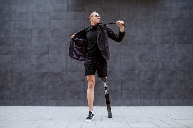 灰色の壁の前で屋外に立っている間、仕事に飽きて彼のスーツを引き裂く義足のハンサムな白人実業家の全長。スポーツの時間です。