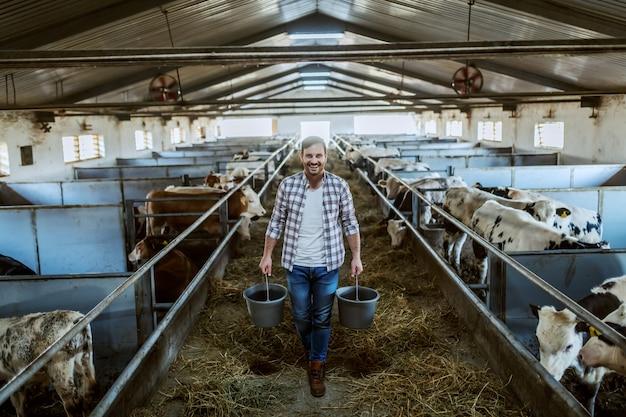 Во всю длину красивого кавказского фермера в клетчатой рубашке и джинсах держит ведра в руках с кормом для животных. стабильный интерьер.